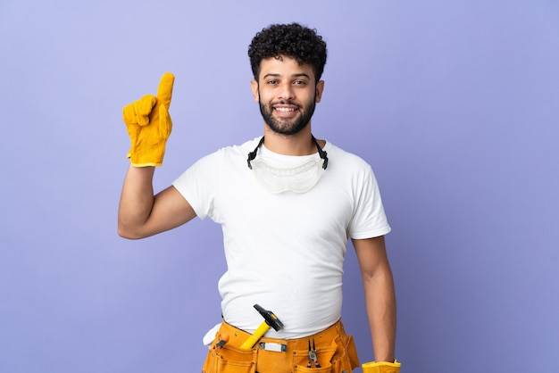 Young electrician moroccan man isolated on purple pointing up a great idea