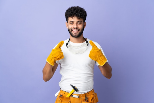 Young electrician moroccan man isolated on purple wall giving a thumbs up gesture