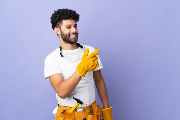Young electrician moroccan man isolated on purple wall pointing finger to the side and presenting a product