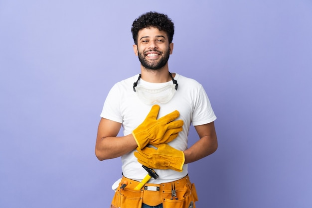 Young electrician moroccan man isolated on purple wall smiling a lot