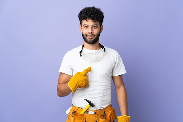 Young electrician moroccan man isolated on purple wall with surprise facial expression