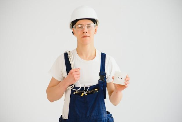 Молодой электрик на белом фоне. держит кабель и розетки.