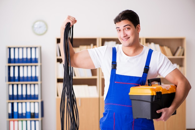 Young electrician with cable working in office