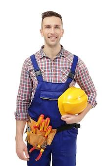 白い背景の上のツールとヘルメットを持つ若い電気技師