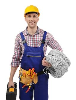 白い背景の上のツールとワイヤーを持つ若い電気技師