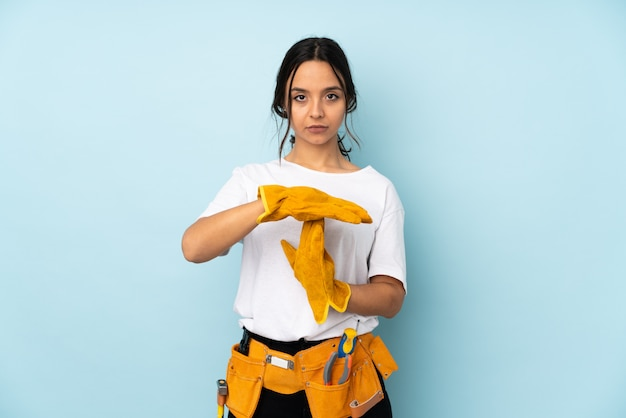 Young electrician woman on blue making time out gesture