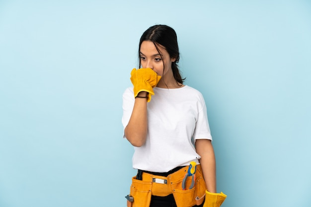 Young electrician woman on blue wall having doubts
