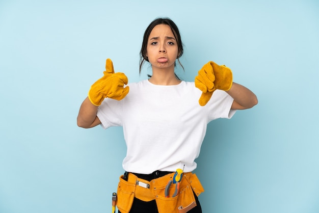 Young electrician woman isolated on blue background making good-bad sign. undecided between yes or not