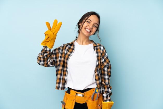 幸せな水色の壁と指で3つを数えるに分離された若い電気技師女性