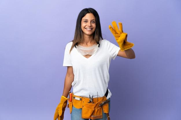 보라색 벽에 고립 된 젊은 전기 여자 행복 하 고 손가락으로 세 세
