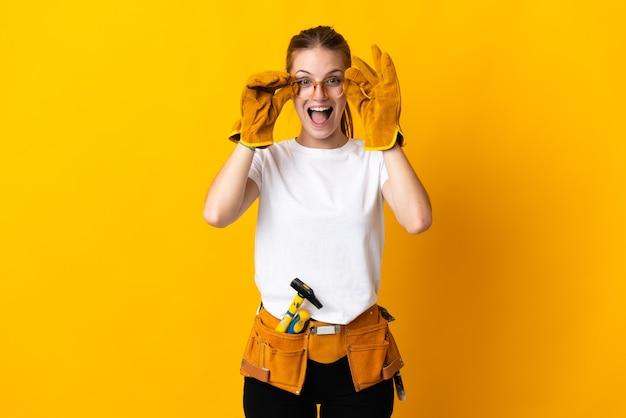 眼鏡で黄色の壁に隔離され、驚いた若い電気技師の女性