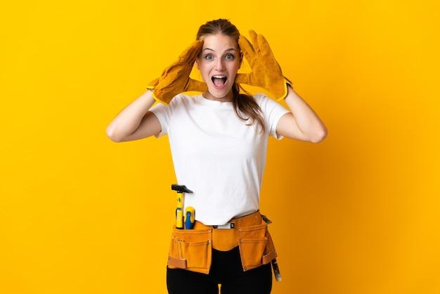 Молодая женщина-электрик изолирована на желтом с удивленным выражением лица