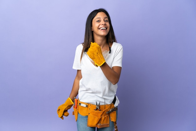 Young electrician woman isolated on purple background celebrating a victory