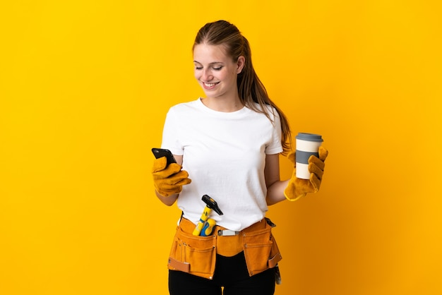 Young electrician woman isolated on yellow background holding coffee to take away and a mobile