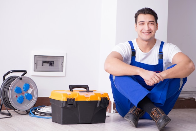 Young electrician working on socket at home