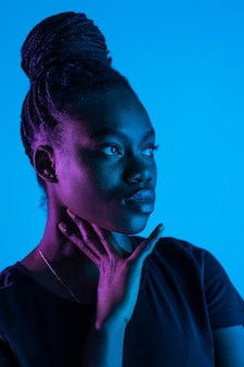 Young elegant african american woman in fashionable neon light space.