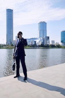 高層ビルで川沿いや街並みに立ち向かいながら、携帯電話で若いエレガントなアフリカのビジネスマンやエージェントコンサルティングクライアント