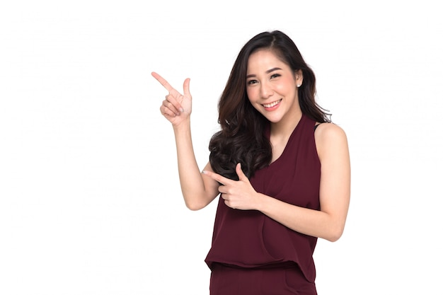 Young elegant asian woman smiling and pointing to empty copy space isolated