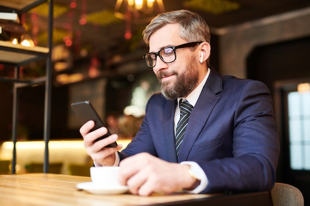 Молодой элегантный бородатый бизнесмен в торжественной одежде, прокручивая в своем смартфоне в уютном кафе или ресторане