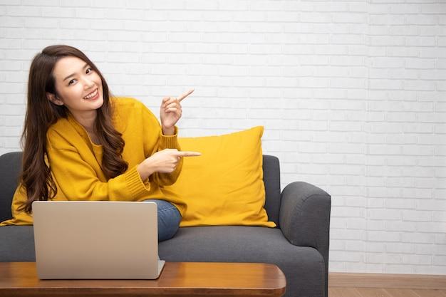젊고 우아한 아시아 여성이 웃고 빈 카피 공간을 가리키며 집 거실에서 노트북과 함께 소파에 앉아 있다