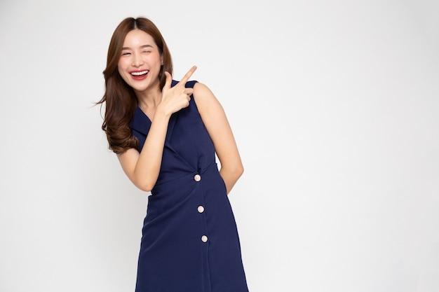 흰색 배경에 격리된 빈 복사 공간을 가리키며 웃고 있는 젊고 우아한 아름다운 아시아 여성