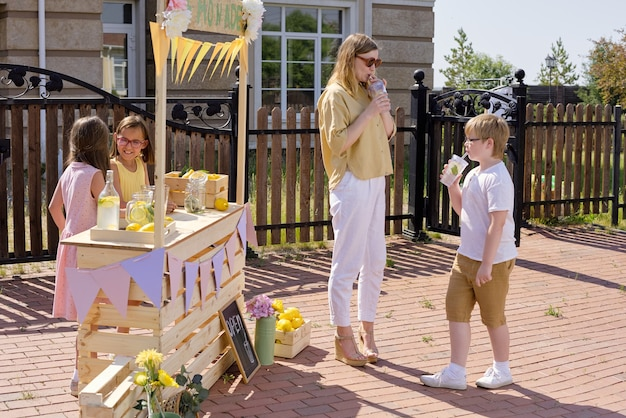 Young elegant blond woman and her little son drinking fresh homemade lemonade while standing by wooden stall with two girls