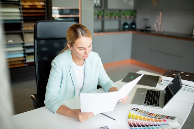 Young elegant blonde businesswoman reading text of contract on two papers before signing it