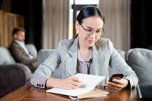 Молодая элегантная брюнетка-бизнесвумен прокручивает смартфон, делая рабочие заметки в тетради за столиком в кафе
