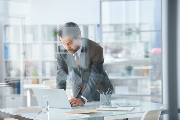 Young elegant businessman bending over desk and laptop while browsing in the net in office