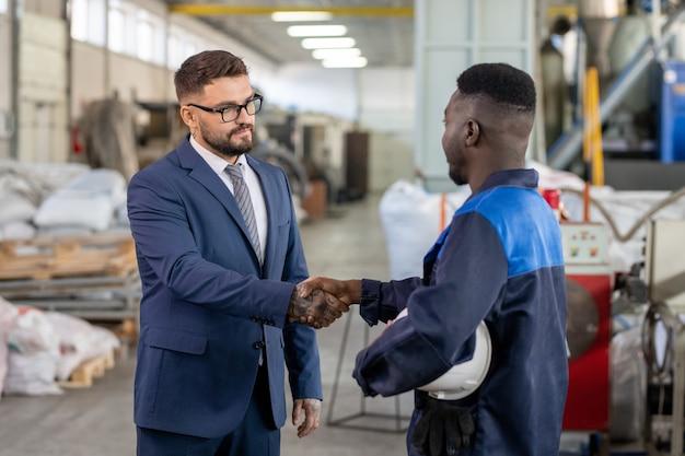Молодой элегантный бизнесмен в костюме и очках, пожимая руку африканского рабочего крупного промышленного предприятия после заключения сделки и подписания контракта