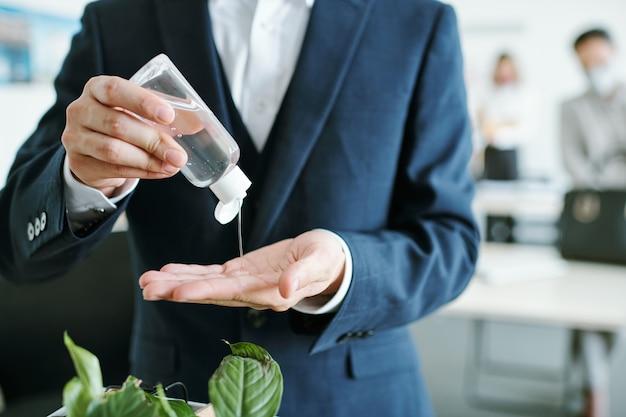 Молодой элегантный бизнесмен в костюме капает дезинфицирующее средство из пластиковой бутылки на руках в начале рабочего дня в офисе