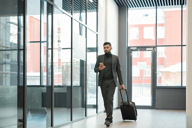 Young elegant businessman scrolling in smartphone while moving along airport and pulling suitcase with luggage