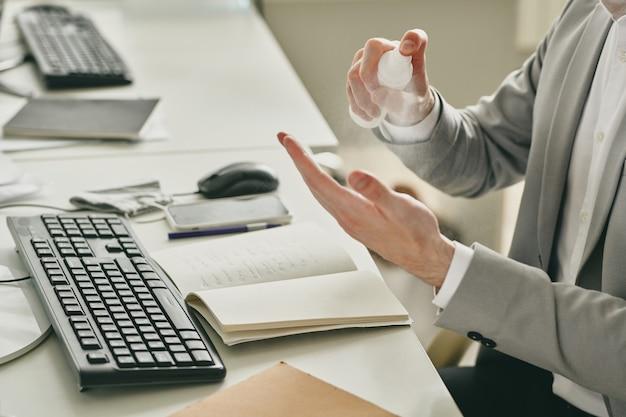 사무실에서 컴퓨터 앞에 책상에 앉아 작업을 시작하는 동안 그의 손에 소독제를 살포하는 젊은 우아한 사업가