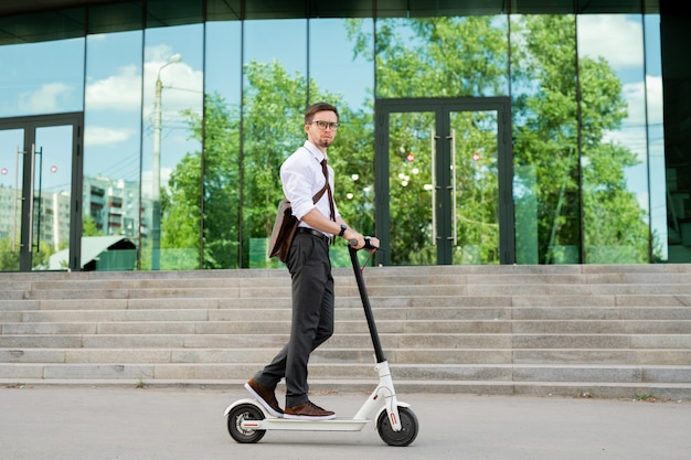 スクーターの上に立って、背景に建物の外観と道を下ってカフェや家に移動する若いエレガントなビジネスマン