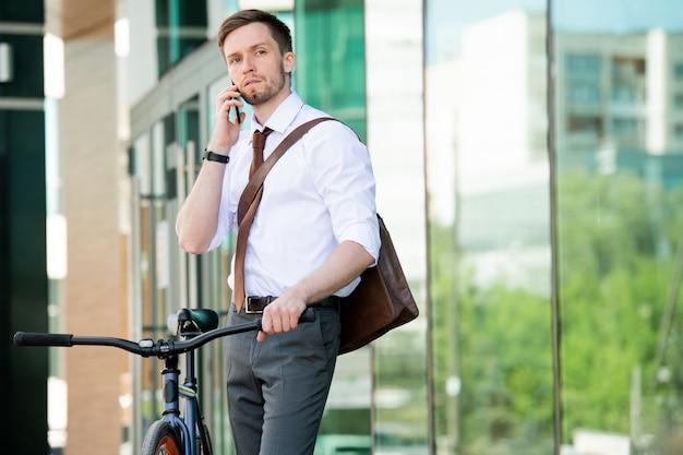 Молодой элегантный бизнесмен разговаривает с кем-то с помощью смартфона, держа велосипед