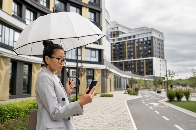 비오는 날씨에 화상 채팅으로 의사 소통하는 젊은 우아한 사업가