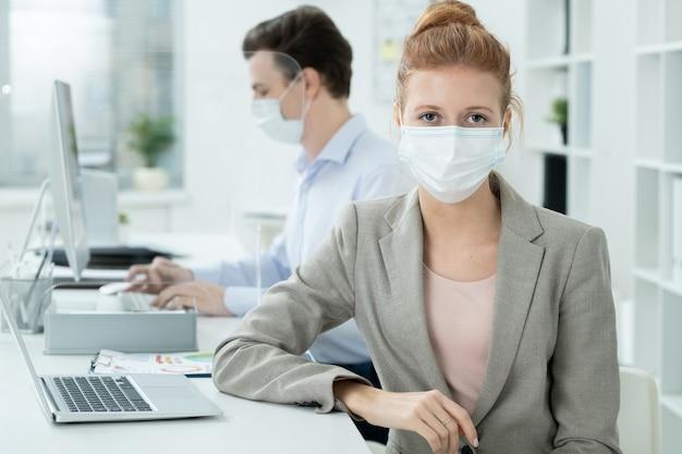 Молодая элегантная деловая женщина в защитной маске смотрит на вас на фоне своего коллеги-мужчины, анализирующего онлайн-данные