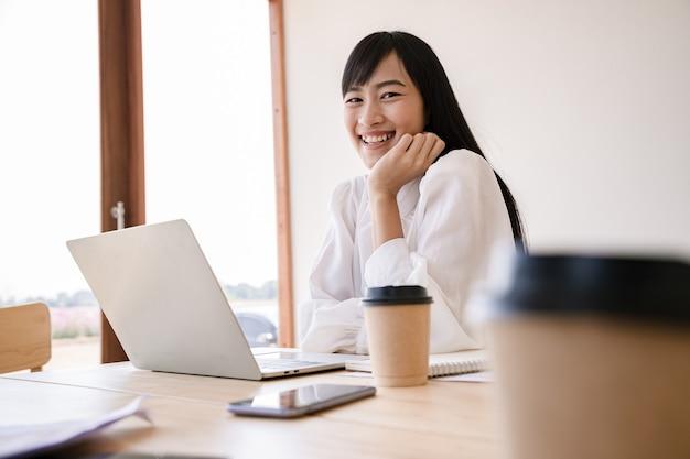 흰 셔츠와 카페에서 노트북과 함께 앉아 커피 한잔에 젊은 우아한 사업가. 긍정적 인 생각 사람 개념을 꿈꾸며.