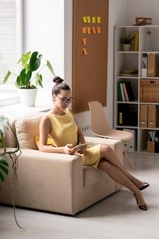 オフィスの窓際の柔らかく快適なアームチェアに座ってスマートフォンでスクロールする若いエレガントな実業家