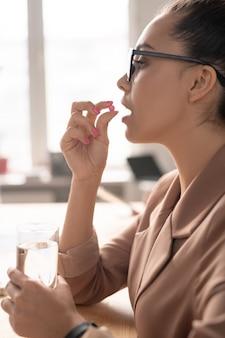 Молодая элегантная деловая женщина со стаканом воды собирается принять таблетку или витамин, держа ее во рту