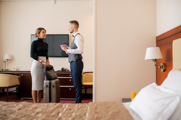 Young elegant businesswoman with suitcase and handbag standing in hotel room in front of porter during talk