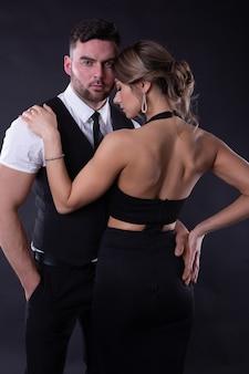 Молодая элегантная пара в черной одежде позирует