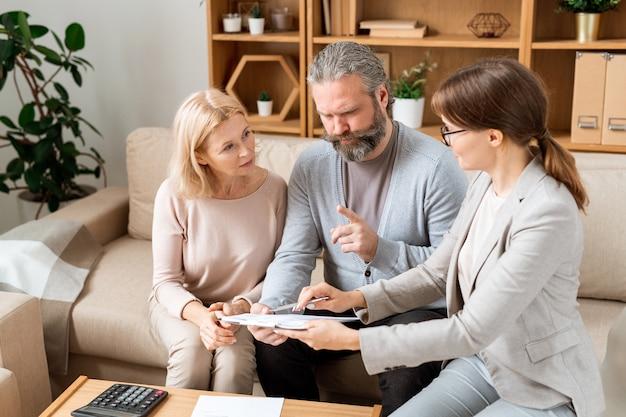 Молодая элегантная женщина-агент консультирует зрелого мужчину и женщину и объясняет пункты контракта на встрече