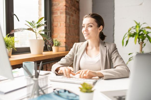 Молодая элегантная сотрудница смотрит на экран компьютера во время набора текста на клавиатуре за столом в рабочий день