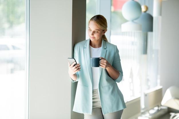 Молодая элегантная женщина-менеджер читает уведомление в смартфоне и пьет кофе во время перерыва в кафе