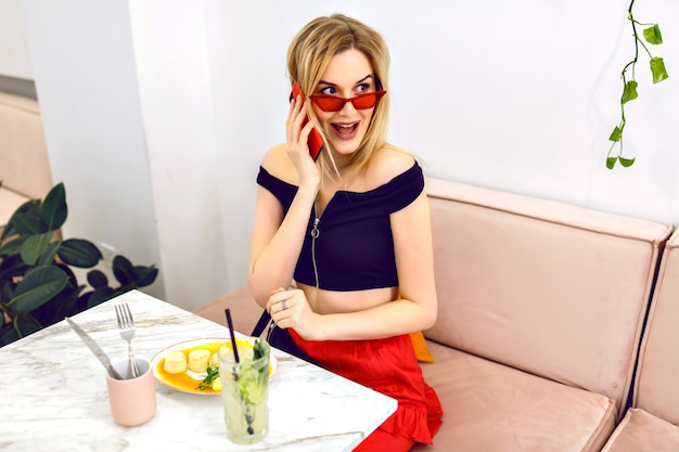 Молодая элегантная девушка позирует в современном городском кафе, разговаривает с бойфрендом по телефону и наслаждается завтраком, счастливые эмоции.