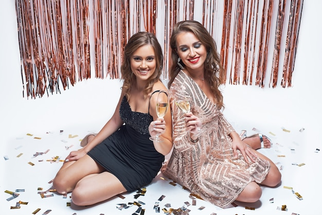 Young elegant girls having fun and drinking champagne during new year party.
