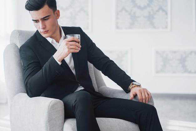 Молодой элегантный парень в черном костюме сидит на белом стуле и держит стакан с алкоголем.