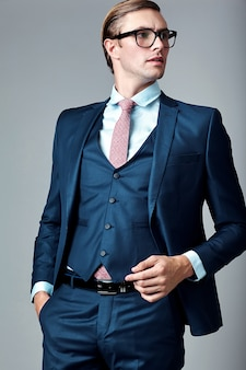 Young elegant handsome businessman male model in blue suit and fashionable glasses, posing in studio