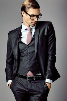 スーツとファッショナブルなメガネの若いエレガントなハンサムな実業家男性モデル